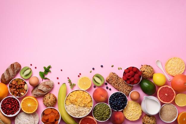 Healthy breakfast ingredients, food frame. oat and corn flakes, eggs, nuts, fruits, berries, toast, milk, yogurt, orange, banana, peach on pink background.