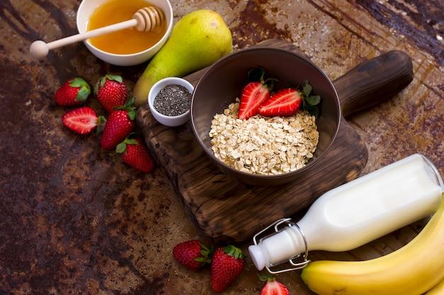 건강한 아침 식사 재료: 오트밀, 꿀, 과일, 딸기, 치아 씨. 복사 공간입니다. 천연 유기농 식품의 개념