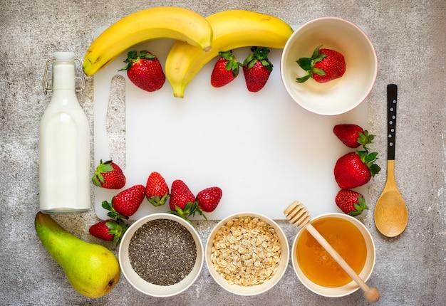 건강한 아침 식사 재료:오트밀, 꿀, 과일, 딸기, 치아 씨앗.복사 공간이 있는 최고 전망. 천연 유기농 식품의 개념입니다.