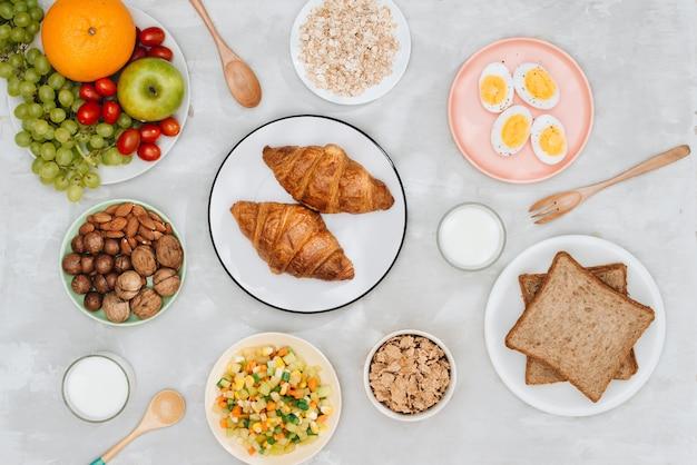 Ингредиенты здорового завтрака на черном фоне бетона. овсяные хлопья, миндальное молоко, орехи, фрукты и ягоды.