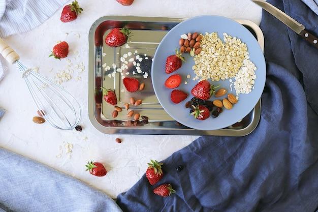 テーブルの上の健康的な朝食の材料イチゴオートミールと明るい背景の上のナッツ