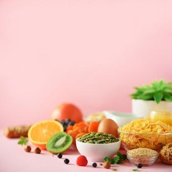 Healthy breakfast ingredients. square crop. oat and corn flakes, eggs, nuts, fruits, berries, toast, milk, yogurt, orange, banana, peach on pink background. copy space