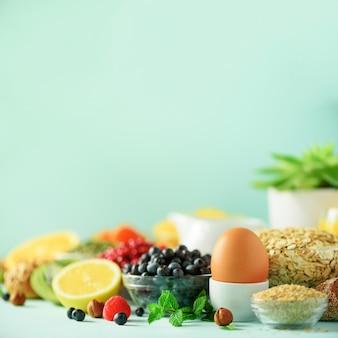 Healthy breakfast ingredients. square crop. oat and corn flakes, eggs, nuts, fruits, berries, toast, milk, yogurt, orange, banana, peach