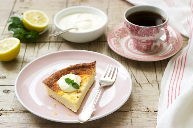 Healthy breakfast made from soft cottage cheese casserole with oatmeal and lemon zest, served with sour cream and mint.