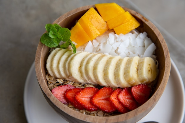 신선한 과일과 함께 나무 그릇에 스무디 그릇으로 만든 건강한 아침 식사
