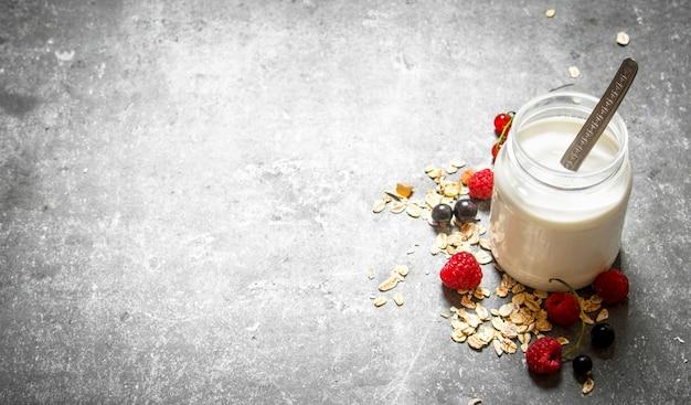 健康的な朝食。シリアルとベリーのミルククリーム。石のテーブルの上。