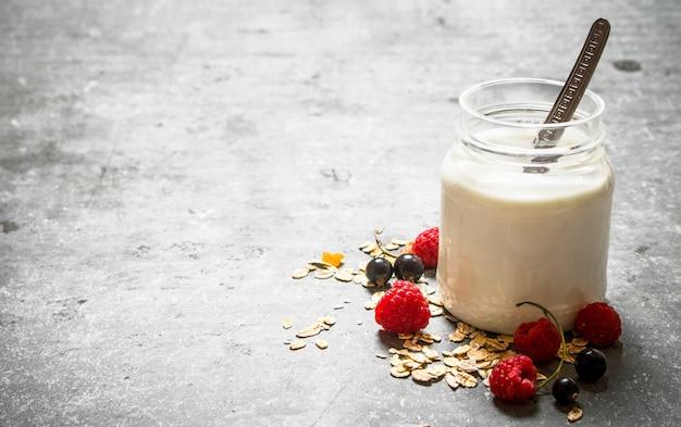 Здоровый завтрак . крем молочный с хлопьями и ягодами. на каменном столе.