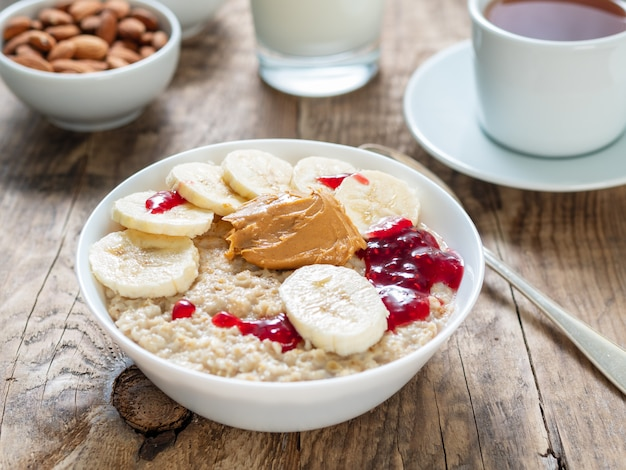 Healthy breakfast in the morning - oatmeal with slices of bananas, raspberry jam and peanut butter.