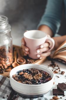 ヘルシーな朝食、ベリーとオレンジジュースのミューズリーをガラスのテーブルと本でお召し上がりいただけます。マニキュア