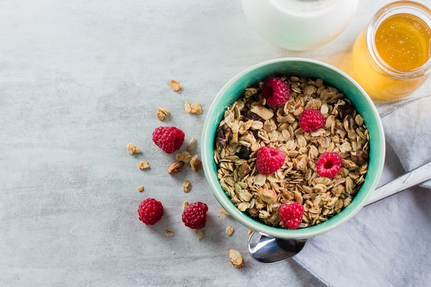 Healthy breakfast. oat granola  milk and honey on white concrete background, top view