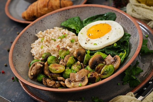 Healthy breakfast. oat porridge, egg and salad of baked vegetables - mushrooms and brussels sprouts..