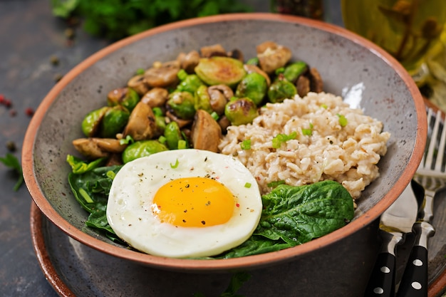 Healthy breakfast. oat porridge, egg and salad of baked vegetables