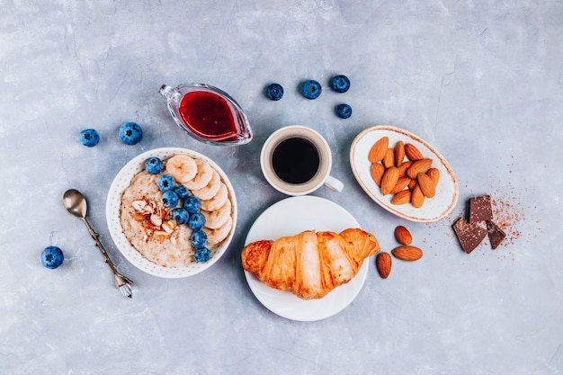 Healthy breakfast - oatmeal, croissant and coffee