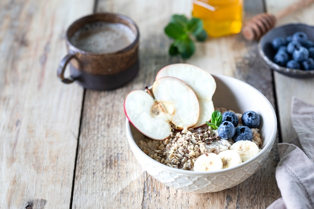 Healthy breakfast, oatmeal or granola with blueberries, apple and honey on a rustic wooden background. copy space