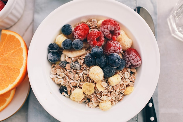 Healthy breakfast: oatmeal with  raspberries,oranges and blueberries. homemade granola. healthy breakfast ingredients. bowl of oat granola with milk, fresh fruit. top view, copy space