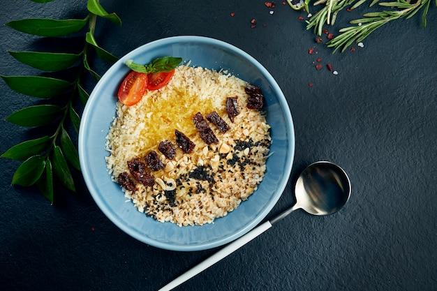 健康的な朝食:オートミール、サンドライトマト、パルメザンチーズ、バター、黒いテーブルの上の青いボウル。トップビュー食品フラットレイアウト。コピースペース