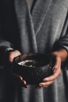 健康的な朝食。ヨーグルトとイチジクを持った女の子の手にあるココナッツボウル。健康食品。ビーガン主義。