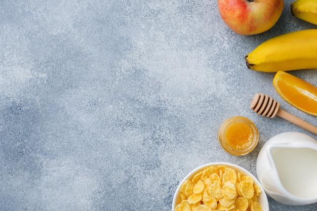 シリアル、ミルク、蜂蜜、フルーツのヘルシーな朝食。バランスの取れた食事。コピースペース