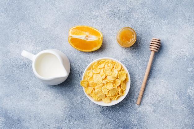 シリアル、ミルク、蜂蜜、フルーツのヘルシーな朝食。バランスの取れた食事。