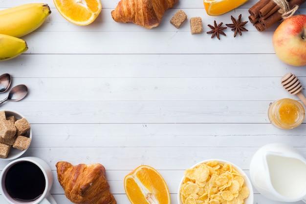 コーヒークロワッサン、ミルク、蜂蜜、フルーツのヘルシーな朝食。バランスの取れた食事。コピースペース