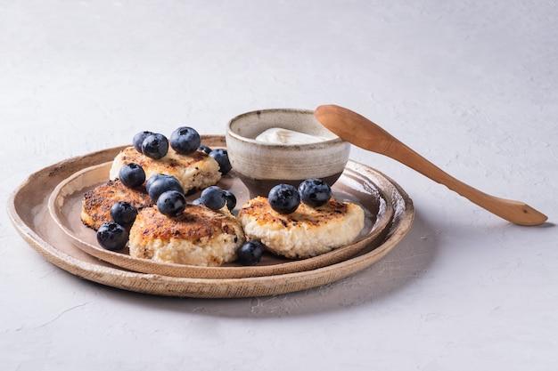 Здоровый завтрак из творожных блинов, сырников с черникой и сметаны крупным планом в тарелке на столе