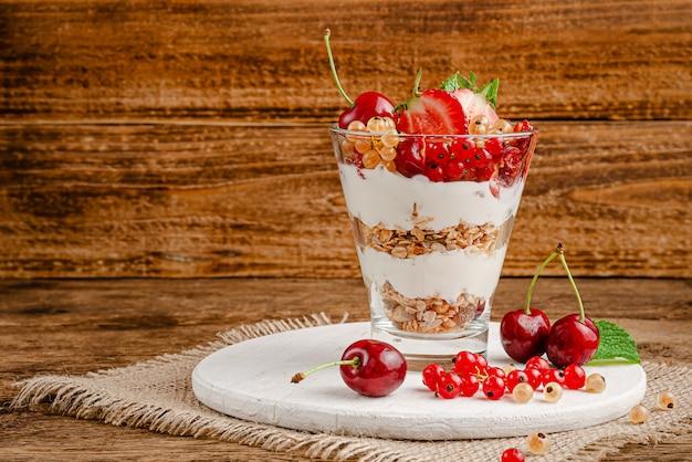 Здоровый завтрак из мюсли с ягодами и йогуртом на деревенском деревянном пространстве. копировать пространство