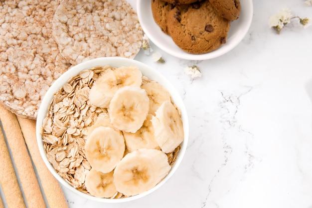 白い背景の上のバナナとオートミールクッキーとオートミールの健康的な朝食