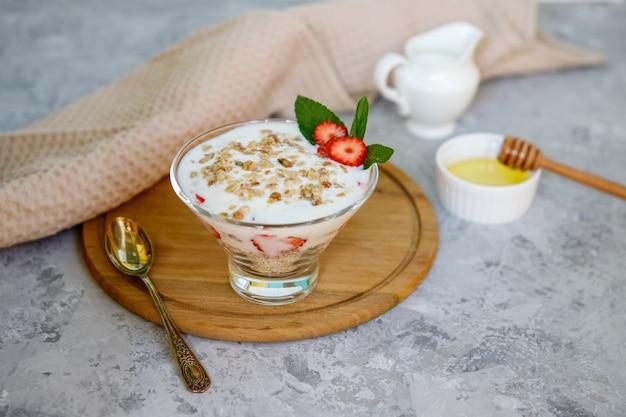 Здоровый завтрак из клубники парфе со свежими фруктами, йогуртом и мюсли на сером столе. овсянка десертная.