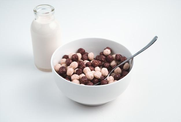 Здоровый завтрак из пшеничных шариков и свежего молока на светлой поверхности. вид сбоку. концепция здоровых, диетических завтраков.