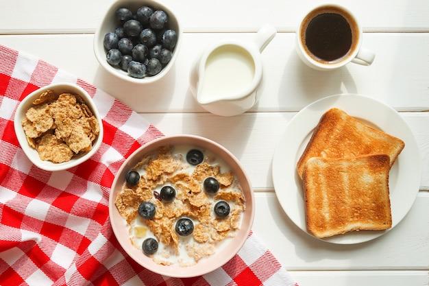 全粒粉フレークのヘルシーな朝食、ミルクブルーベリーコーヒーとトーストのクローズアップ木製テーブル