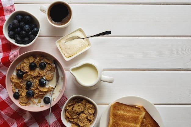 コピースペースのある木製のテーブルで、ミルクブルーベリーのコーヒーとトーストを添えた全粒粉フレークのヘルシーな朝食