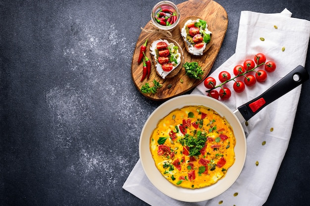 Healthy breakfast of omelet with cherry tomatoes and spinach in frying pan and toast with cottage cheese, pesto sauce and cherry tomatoes on white cloth napkin on black background with copy space