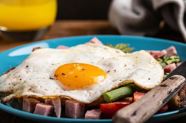 Здоровый завтрак или обед с жареным яйцом, хлебными тостами, зеленой спаржей и помидорами на синей тарелке на старом деревянном столе