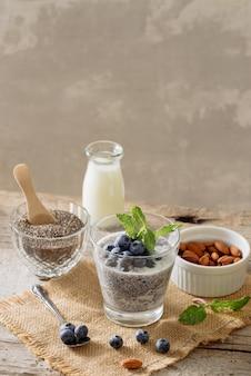 소박한 나무 배경, 채식 음식, 다이어트 및 건강 개념에 치아 씨 푸딩과 베리를 곁들인 건강한 아침 식사 또는 아침 간식