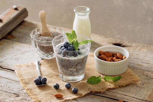 Здоровый завтрак или утренняя закуска с пудингом из семян чиа и ягодами на деревянном деревенском фоне, вегетарианская еда, диета и концепция здоровья