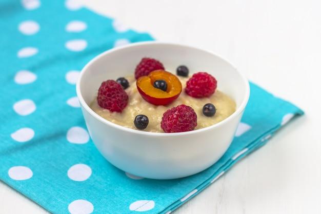 子供のための健康的な朝食のおbreakfast。ファブリック上の離乳食のボウル。適切な栄養と健康食品のコンセプト。