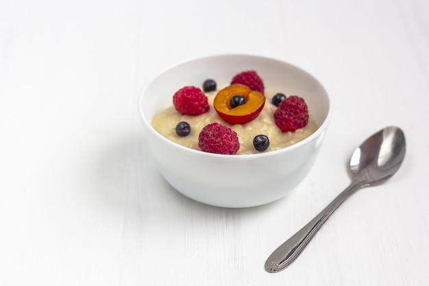 子供のための健康的な朝食のおbreakfast。白い木製の離乳食のボウル