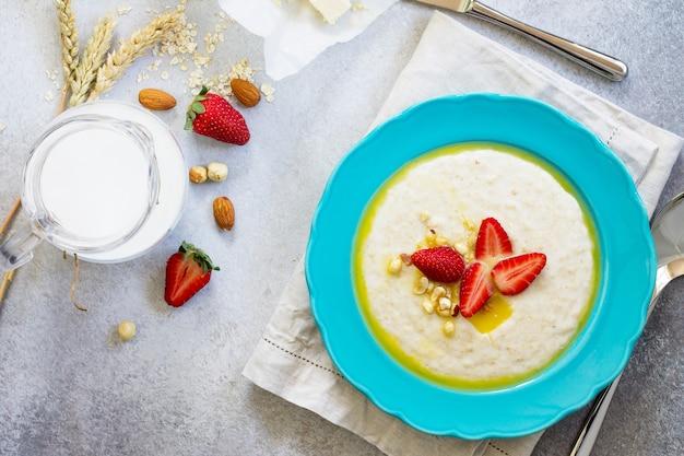 健康的な朝食石の背景にナッツミルクと新鮮なイチゴとオートミールのお粥