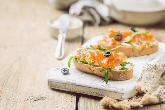 Здоровый завтрак сэндвич с лососем, сливочным сыром и рукколой на деревянном фоне