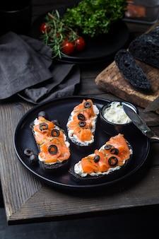 Здоровый завтрак сэндвич с лососем со сливочным сыром и черным хлебом на темном фоне