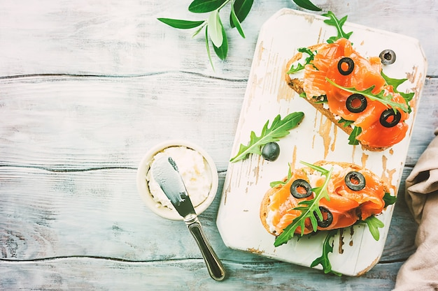 Healthy breakfast salmon sandwich with cream cheese and arugula on wooden background, top view