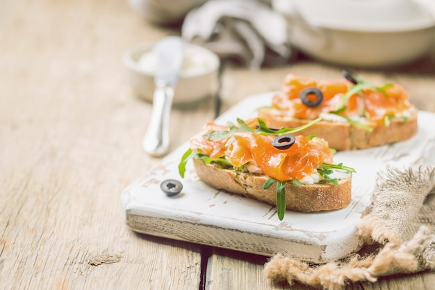 Healthy breakfast salmon sandwich with cream cheese and arugula on wooden background