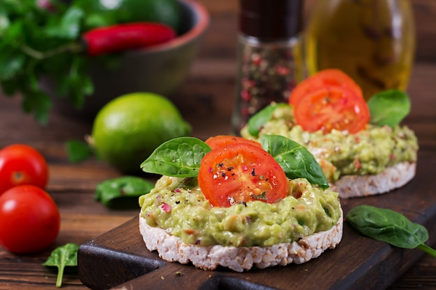 Healthy breakfast. sandwich crisp bread with guacamole and tomatoes on a wooden table.