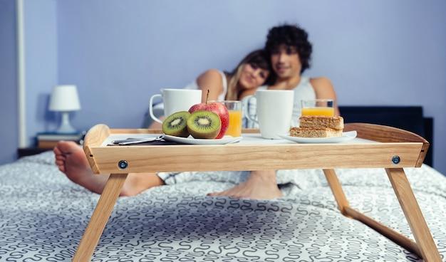 Здоровый завтрак подается на деревянном подносе, готовом к употреблению, и обниматься счастливая влюбленная пара. концепция здорового питания и домашнего образа жизни.