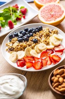 ヘルシーな朝食にヨーグルトミューズリーブルーベリーストロベリーとバナナを添えて。モーニングテーブルグラノーラアーモンドベリー柑橘系フルーツジュースとグリーンハーブ。