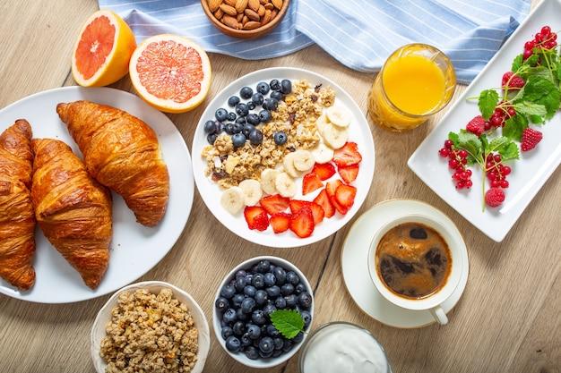 ヘルシーな朝食にヨーグルトミューズリーブルーベリーストロベリーとバナナを添えて。モーニングテーブルグラノーラアーモンドベリー柑橘系フルーツジュースコーヒークロワッサンとグリーンハーブ。