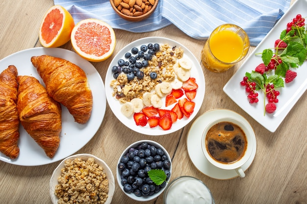 Healthy breakfast served with plate of yogurt muesli blueberries strawberries and banana. morning table granola almonds berries citrus fruits juice coffee croissants and green herbs