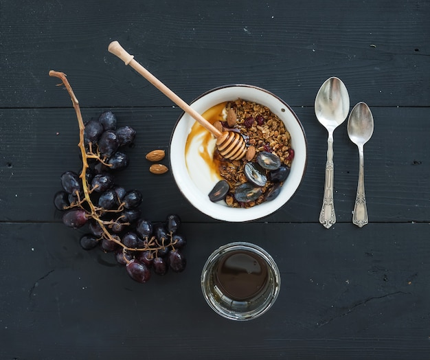 Healthy breakfast set. bowl of oat granola with yogurt, fresh grapes, almond and  honey over black wooden backdrop