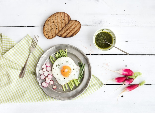 Healthy breakfast set. fried egg with asparagus, radishes, green sauce and bread on vintage metal plate over white wooden table
