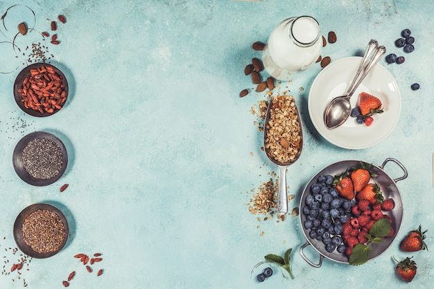 Healthy breakfast set with granola, superfoods, almond milk and berries